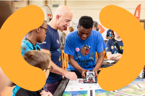 Jeff Bezos looking at robotics project with students