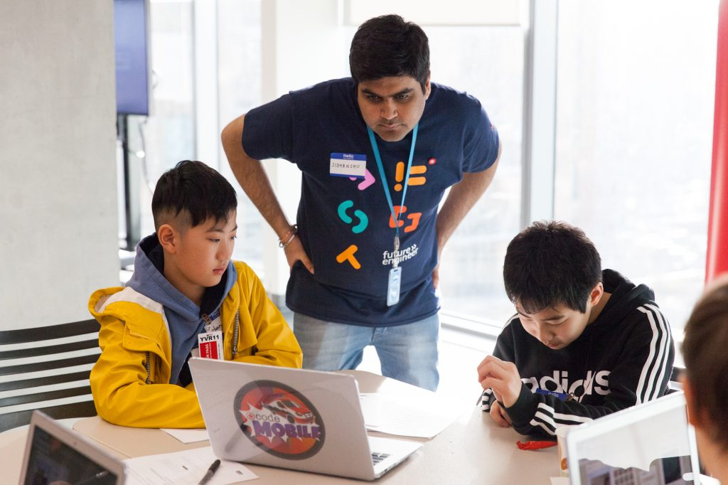 Amazon employee helping two boys at a computer