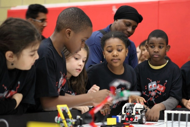 Woman watching a group of kids working on a lego robot