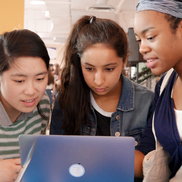 Three girls working at a computer