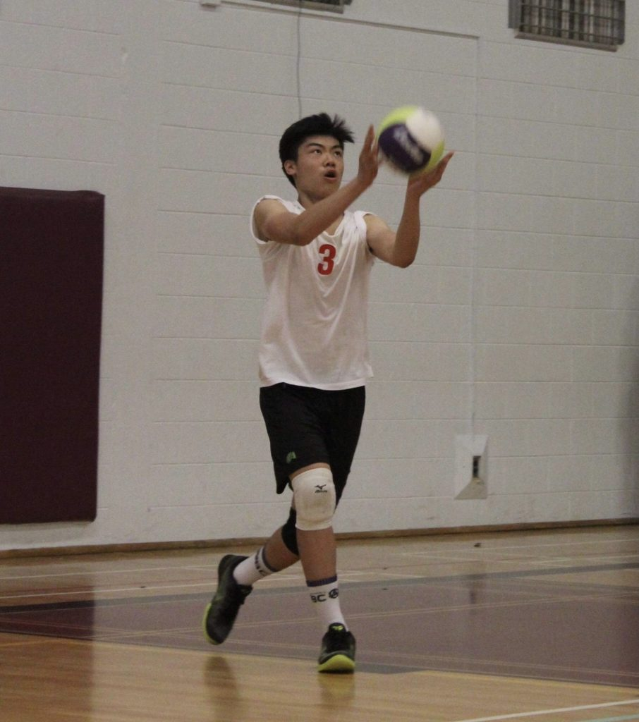 Melvin serviing a volleyball