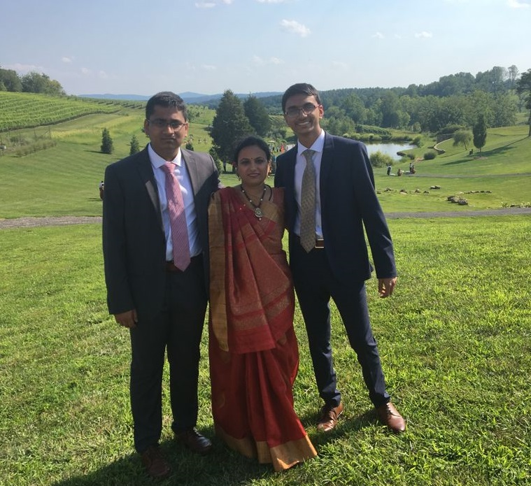 Shivam smiling with his mother and brother